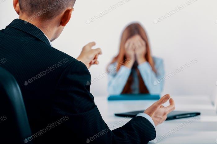 Mujer joven deprimida durante una conversación con el jefe que señala sus errores