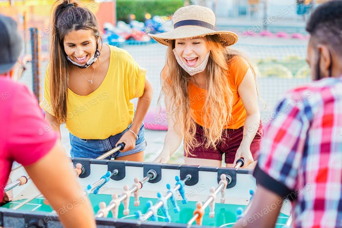 Friends enjoying playing with the table football - Young people with face mask in vacation