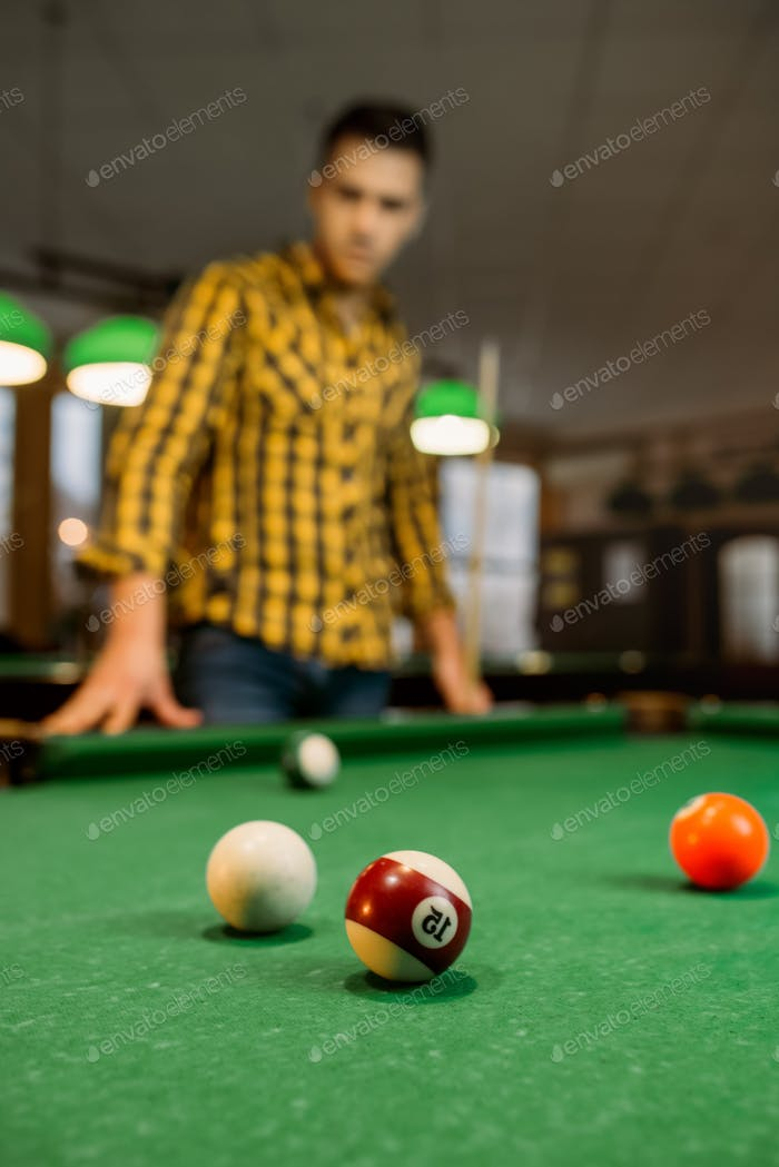 Male billiard player with cue, view from the table