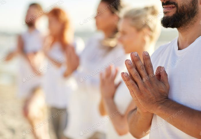 group of people making yoga or meditating on beach