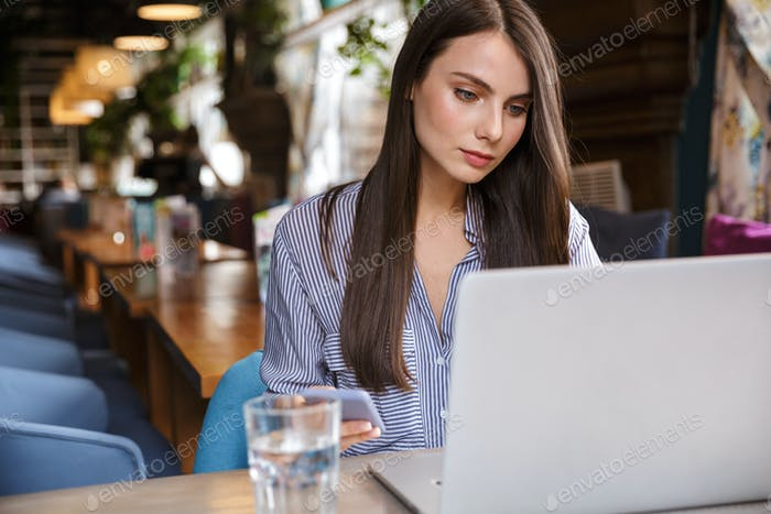 Attractive young brunette woman working on laptop computer
