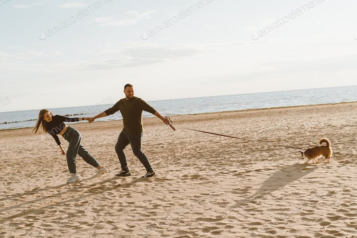 Young happy couple and dog walking on beach. Handsome man holding beautiful woman