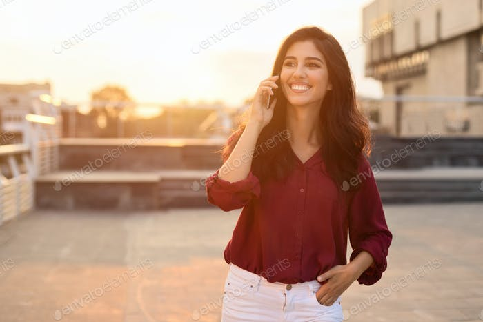 Woman enjoying phone talk outdoors, walking in city