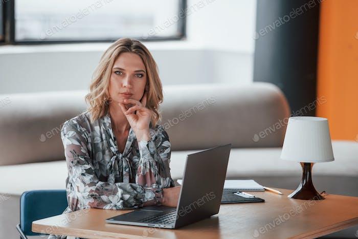 Bauen Sie Ihre Karriere auf. Geschäftsfrau mit lockigen blonden Haaren sitzt im Zimmer vor dem Fenster