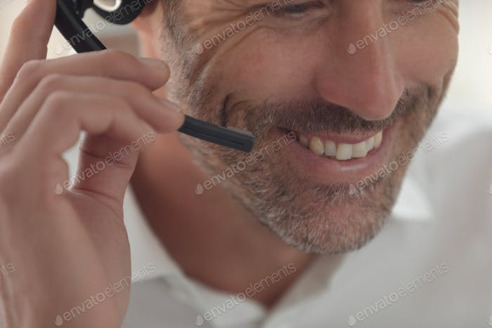 Caucasian male customer service executive talking on headset at desk in a modern office