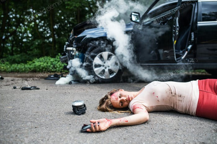 Young injured woman lying on the road after a car accident, unconscious.