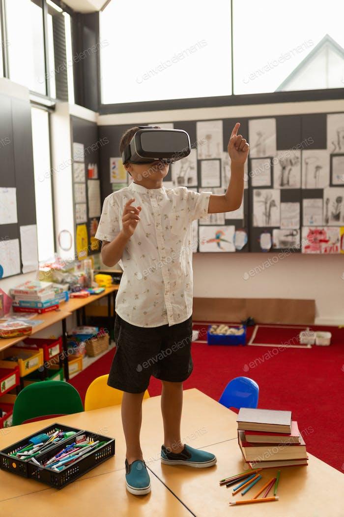 Niedliche gemischte Rennen Schuljunge mit Virtual Reality Headset auf einem Schreibtisch im Klassenzimmer