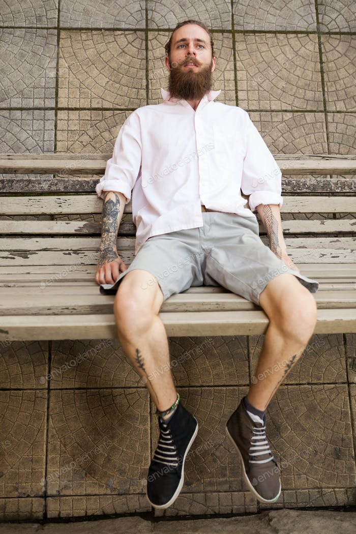Bearded tattooed hipster lying on a bench