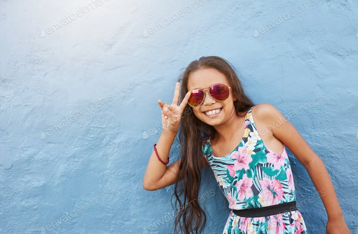 Cute little girl with sunglasses gesturing peace sign