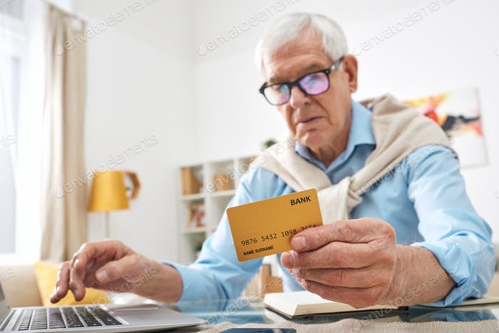 Contemporary retired man holding bank card over table while shopping online