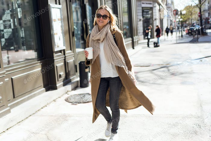 Pretty young woman looking at camera while walking in the street