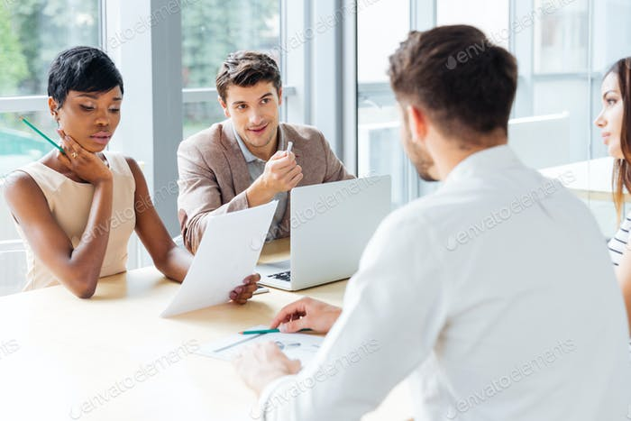 Businesspeople working with laptop at meeting in office