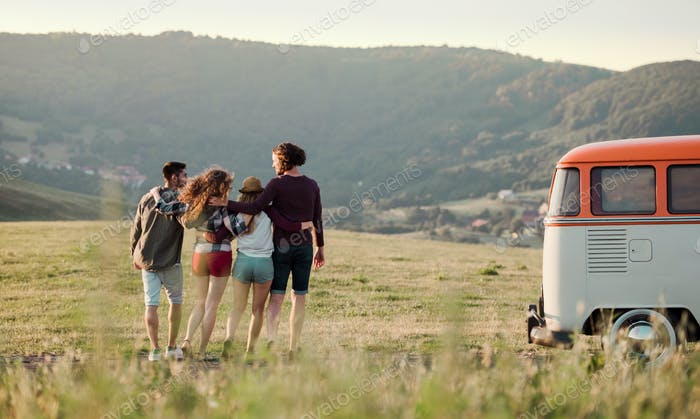 A rear view of group of young friends on a roadtrip through countryside, walking.