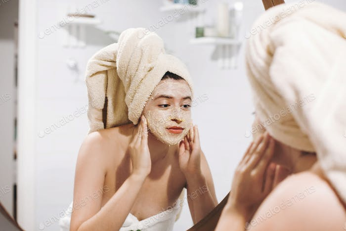 Young happy woman in towel making facial massage with  organic face scrub