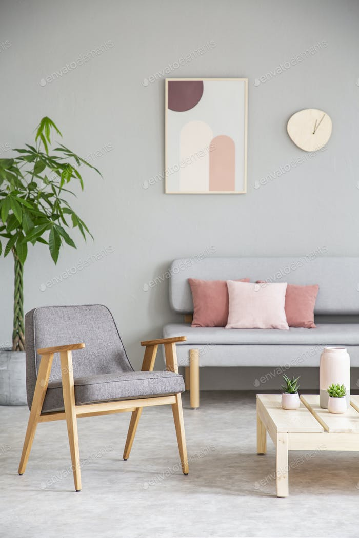Grey wooden armchair next to table in living room interior with