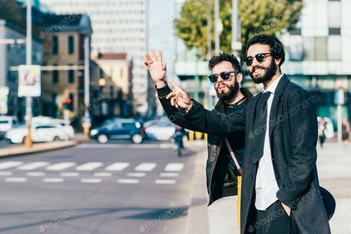 Bearded brown hair businessmen outdoor in the city, asking for a taxi