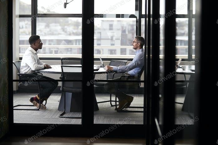 A black and a white businessman meeting for a job interview, full length, seen through glass wall
