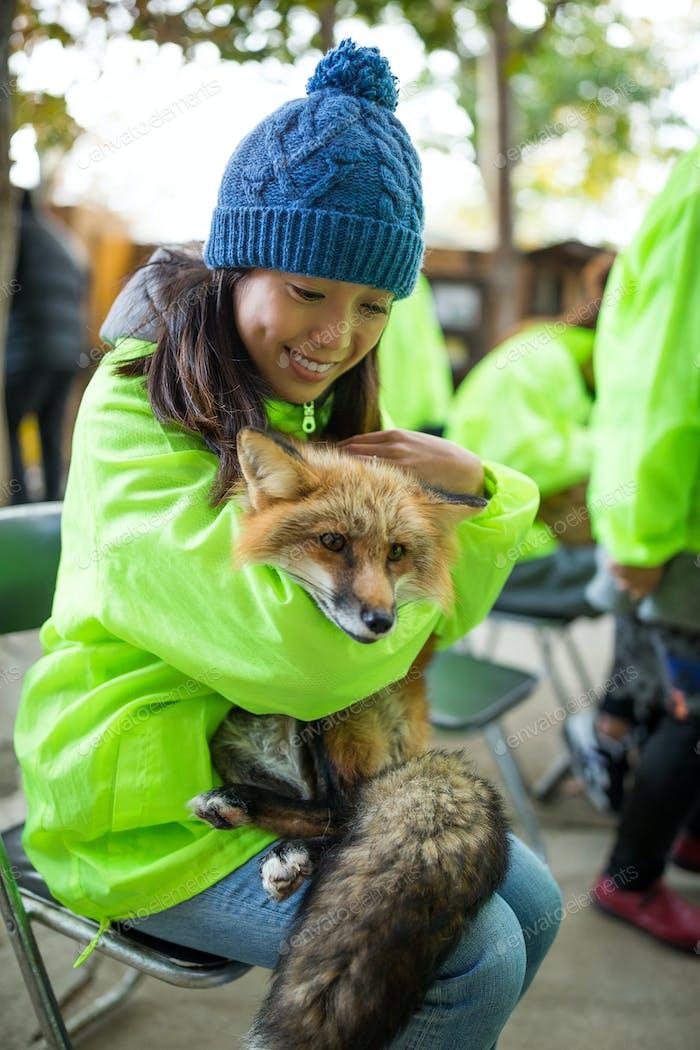 Young woman hugging fox