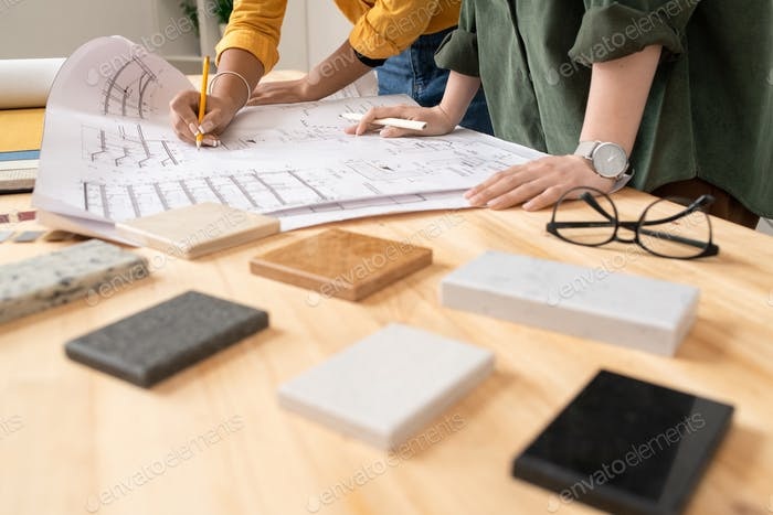 Hands of two young designers of interior bending over apartment plan