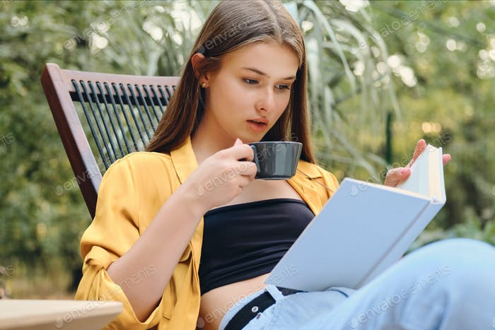 Beautiful brown haired teenage girl in yellow shirt thoughtfully reading book with coffee in park