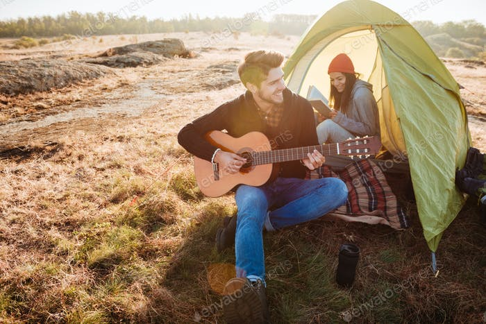 Couple with guitar in tent