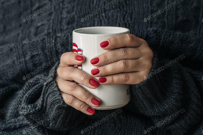 beautiful red manicure with a cup of tea