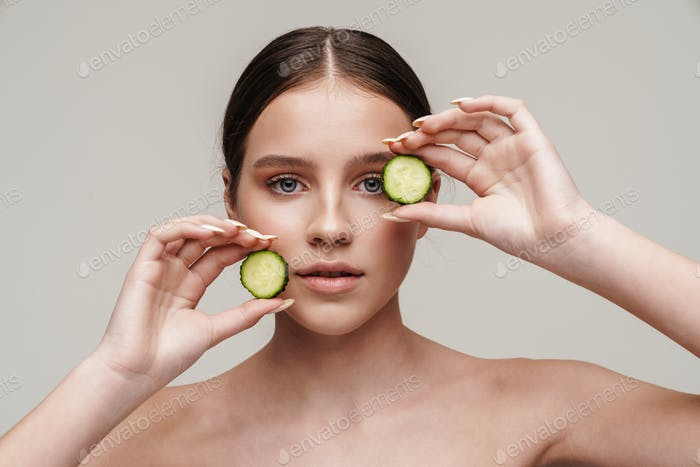 Image of beautiful shirtless woman posing with cucumber at camera