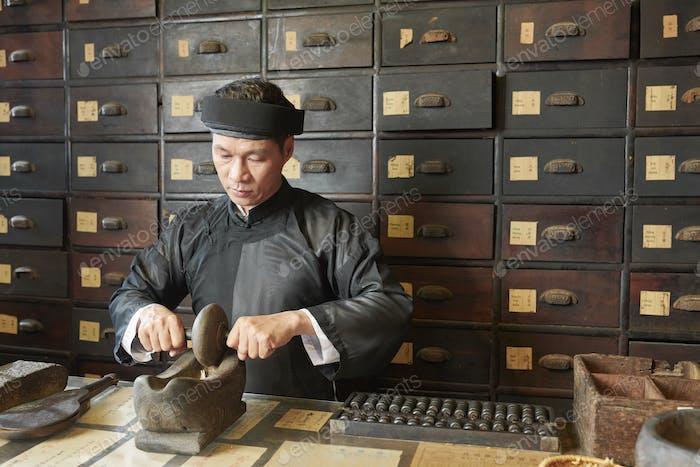 Medicine practitioner pulverizing medicines