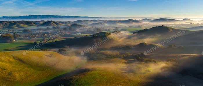 Countryside farm hills and valleys at sunrise with fog, California