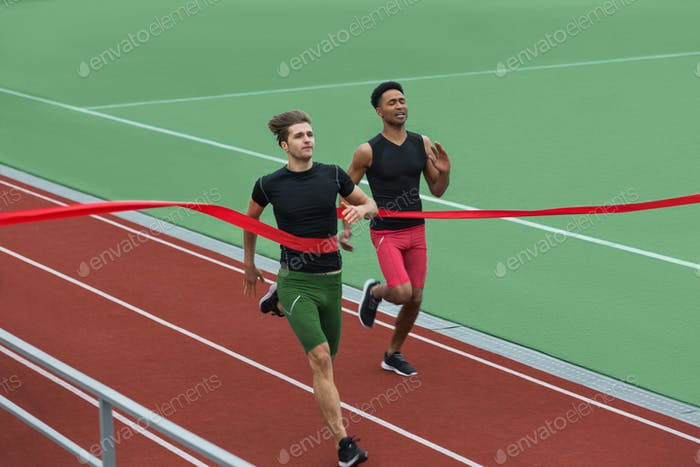Happy young athlete man run on running track