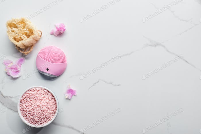 Silicone Cleansing Facial Brush, Bath Salts And Loofah on Marble Surface With Pink Petals