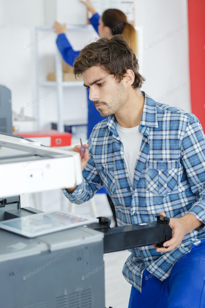 Man repairing office photocopier