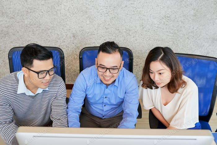 Young employees working with computer in team