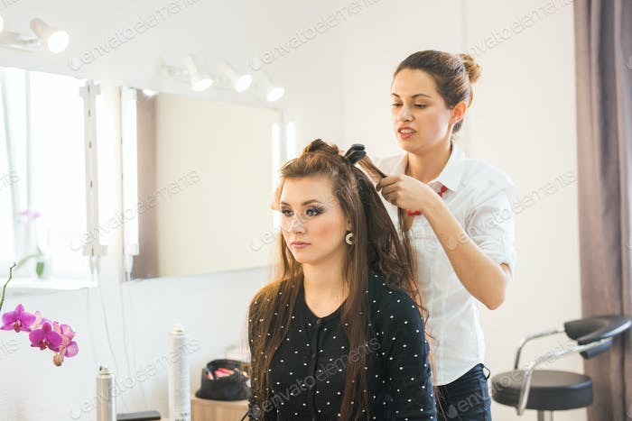 working day inside the beauty salon. Hairdresser makes hair styling