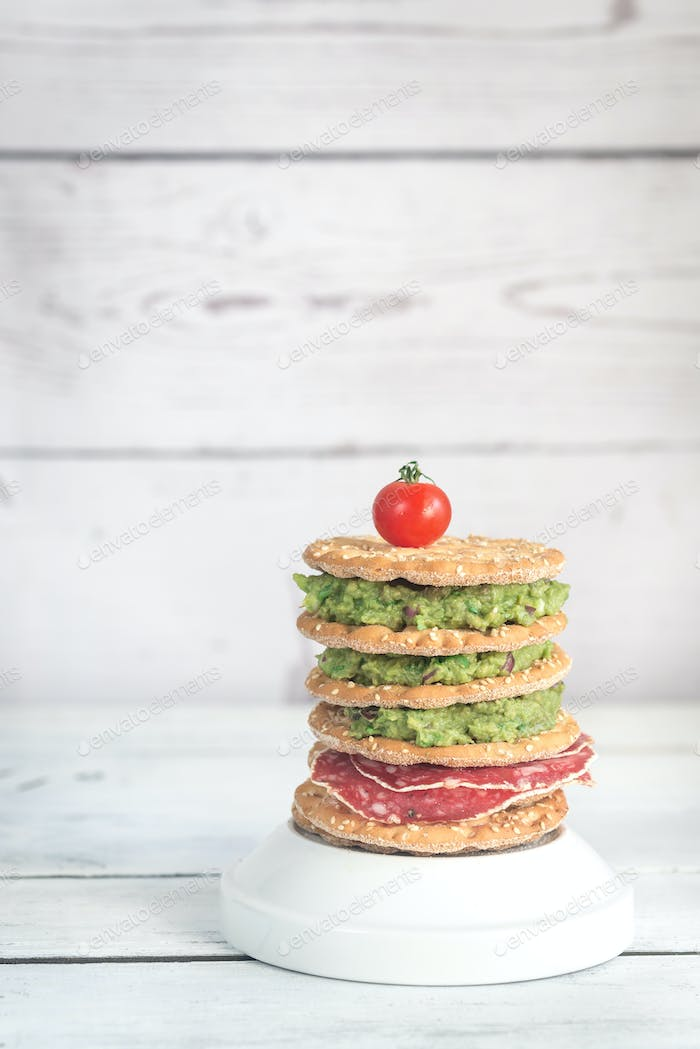 Sesame crispbread with guacamole and smoked sausage