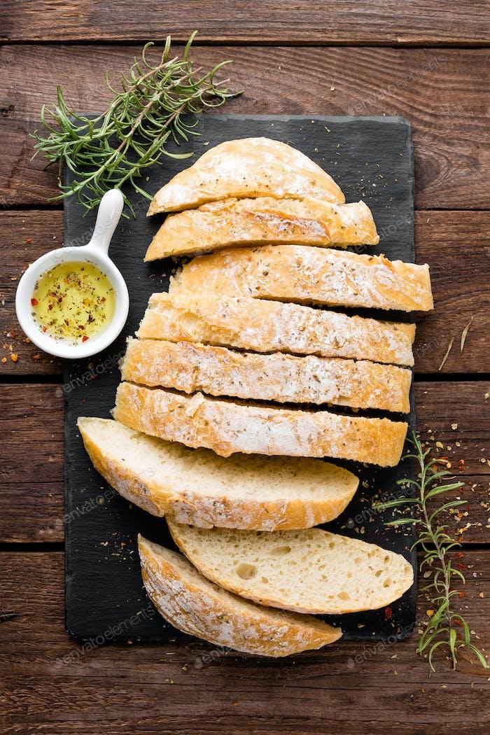 fresh homemade ciabatta bread sliced on stone slate board
