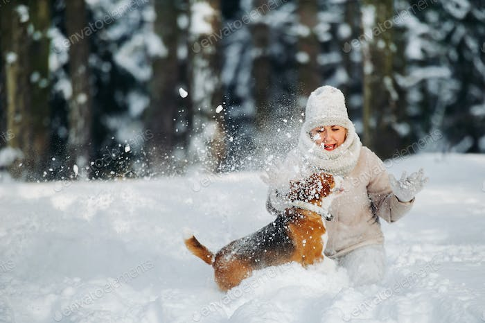 a woman on a walk with her dog in the winter forest. mistress and dog game in the snowy forest
