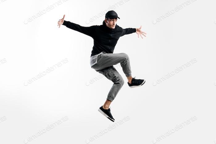 Schöne junge Tänzerin trägt ein schwarzes Sweatshirt, graue Hose und eine Mütze tanzt Breakdance