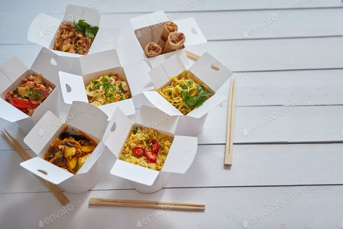 Various oriental dishes packed in paper box. Food is delivered on the table. Asian take away concept