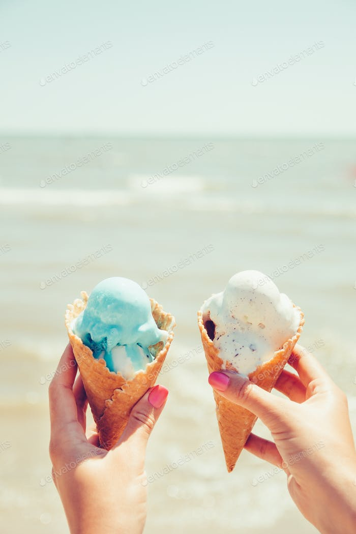 Woman's hands is holding two ice cream on sea