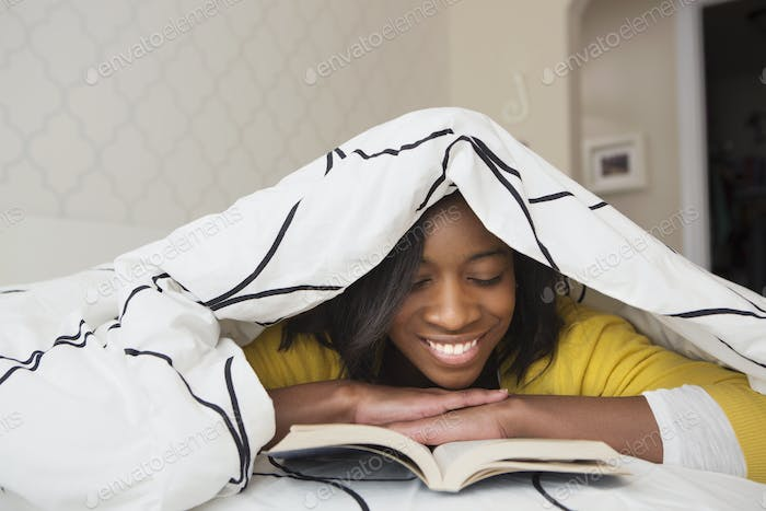 A young girl in her bed, under a duvet reading a book.