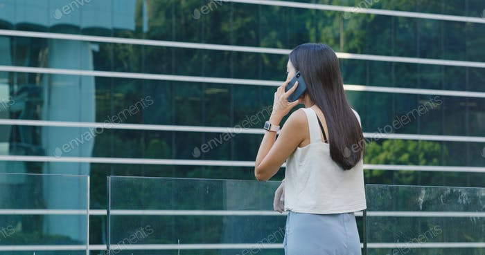 Woman talk to mobile phone in city