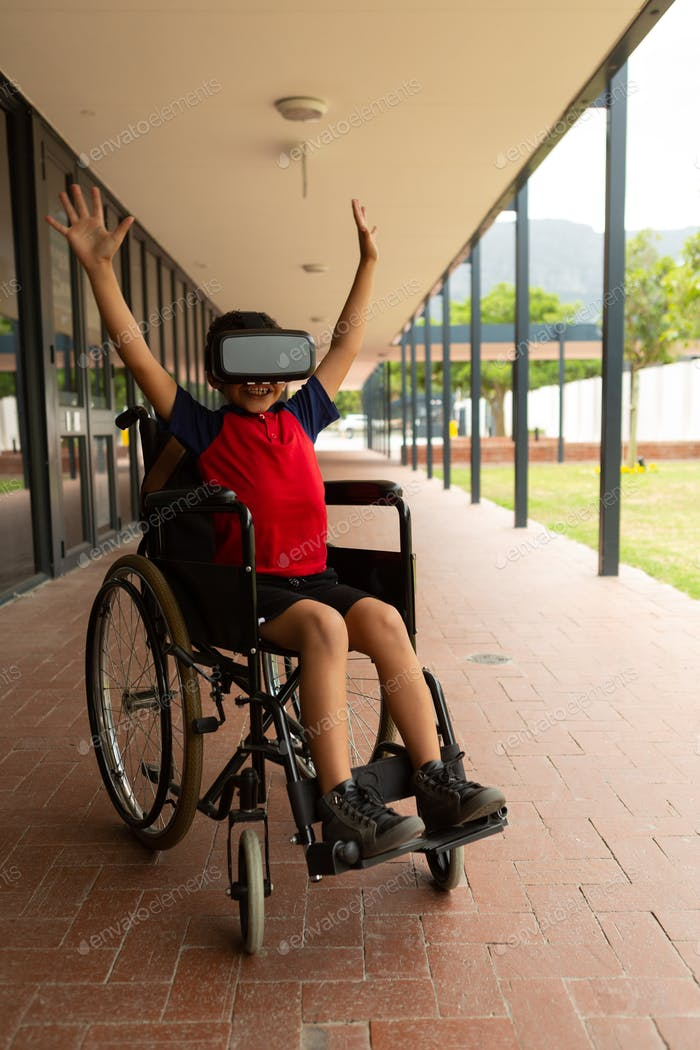 Disabled schoolboy using virtual reality headset in corridor at elementary school