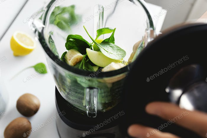 Man cooking smoothie in blender at home