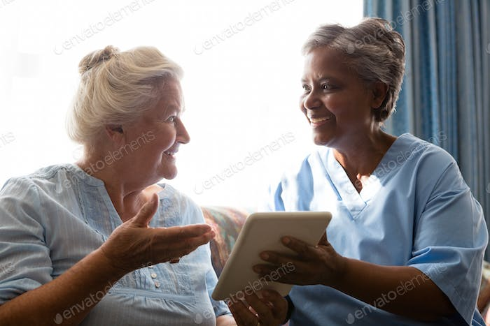 Senior woman and doctor laughing while using digital tablet