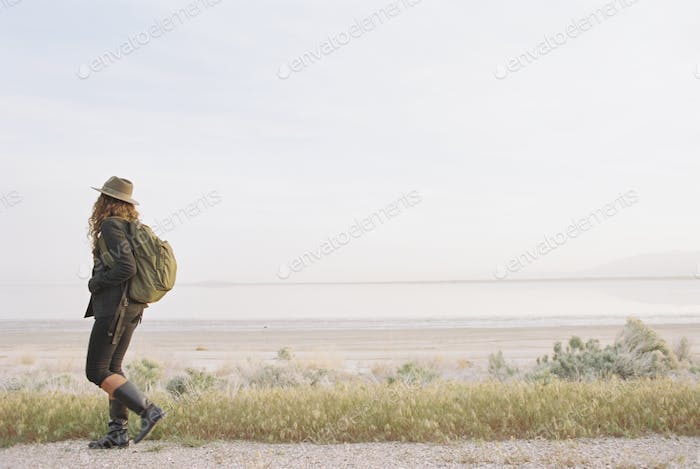 A woman walking along a country road, wearing a hat and carrying a backpack.