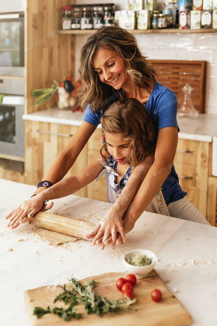 Kleines Kind Mädchen Kneten Teig vorbereiten für das Backen von Keksen.