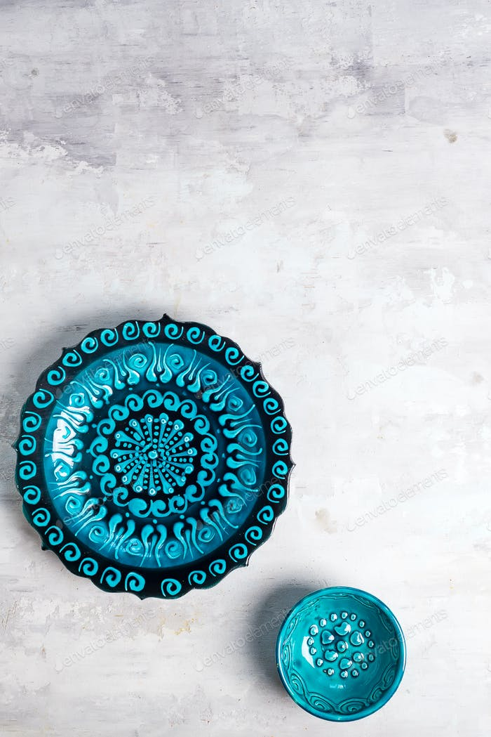 Turkish ceramics decorated blue plate and bowl on stone background, top view