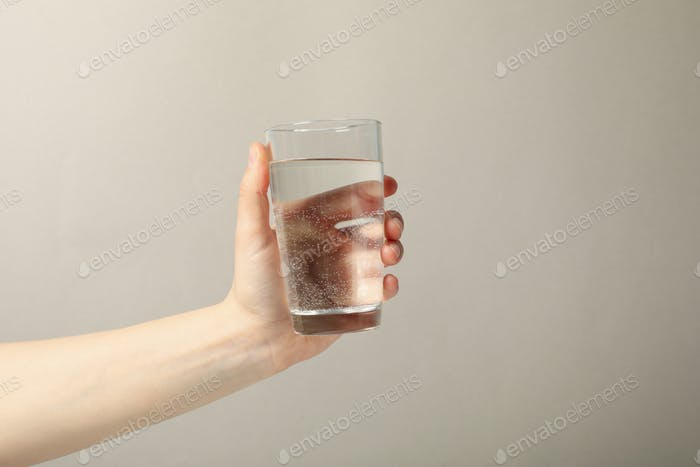Female hand holds glass of water on gray background, close up