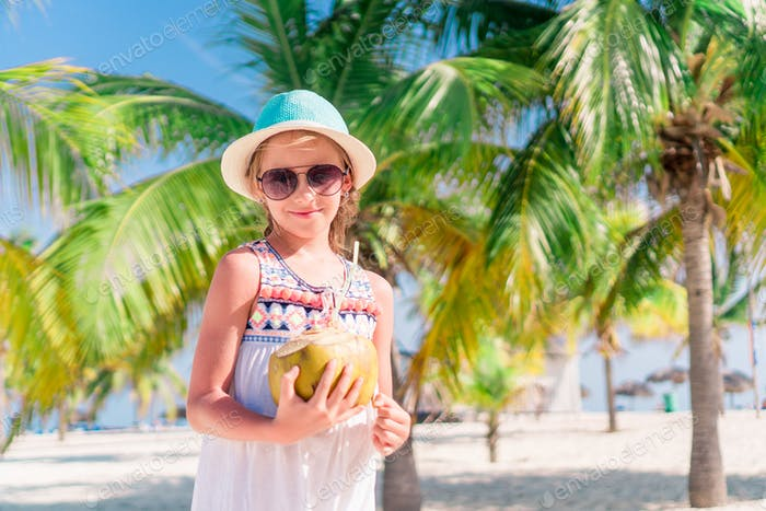 Little adorable girl with big coconut on white sandy beach